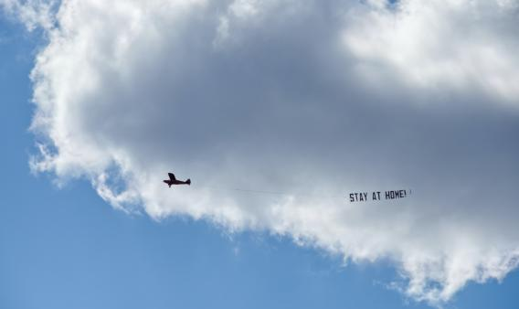 "Avioneta con un cartel con el mensaje ""Stay at home"""