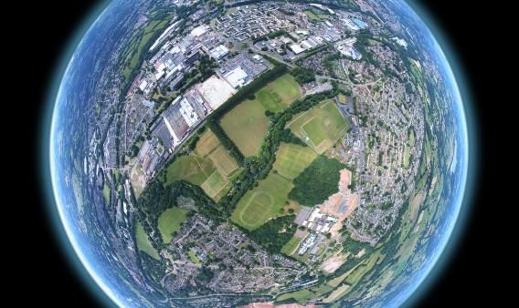 A 360 panorama stitched and warped to create the tiny planet effect. Image sequence taken by drone above a community field in Wales.